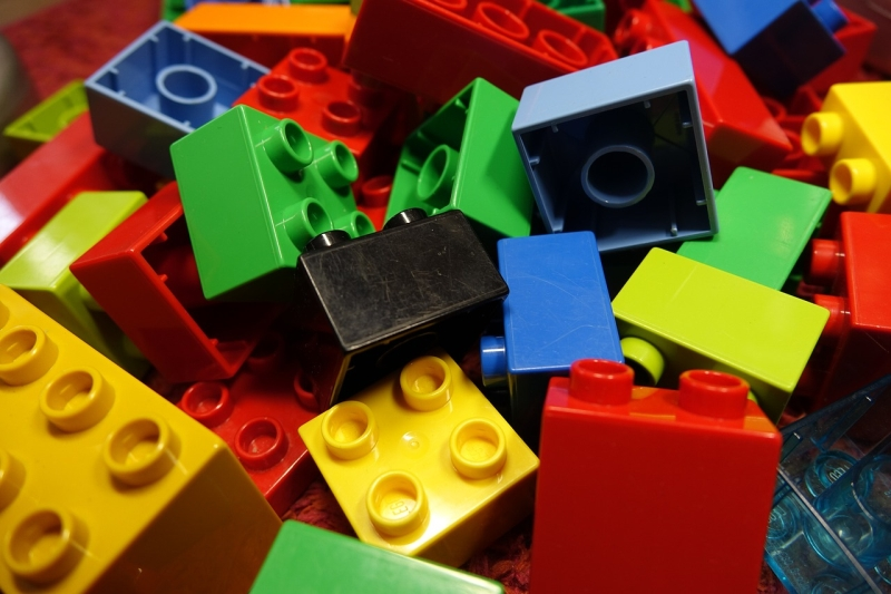 Close up of LEGO building blocks in black, blue, yellow, red, green, and orange